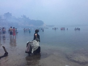 People are seen as a wildfire burns in Mati